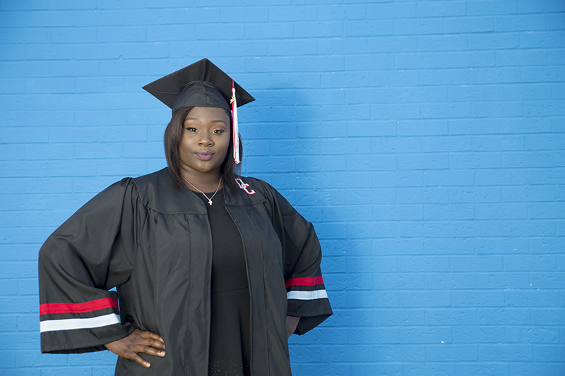 senior posing in front of blue painted brick wall in cap and gown