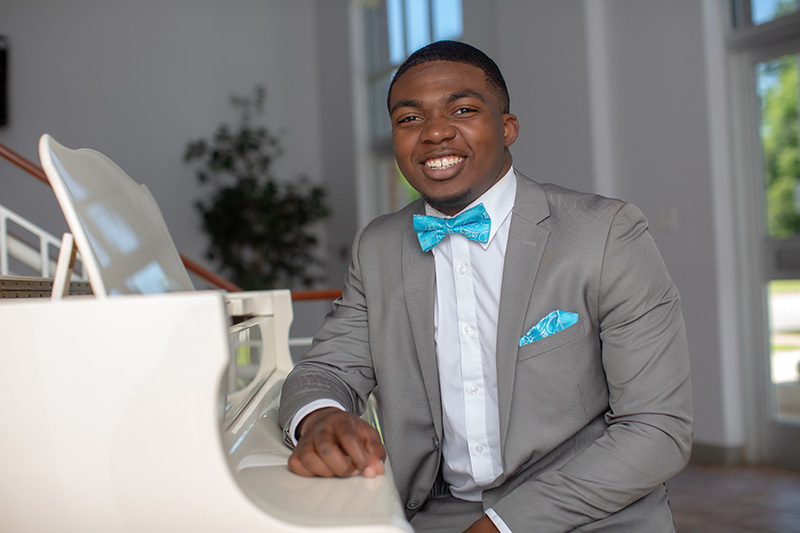 senior posing at piano in suit