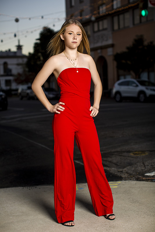 senior posing in red jumpsuit outdoors